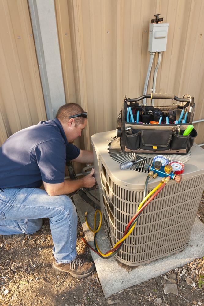 man repairing outdoor ac unit