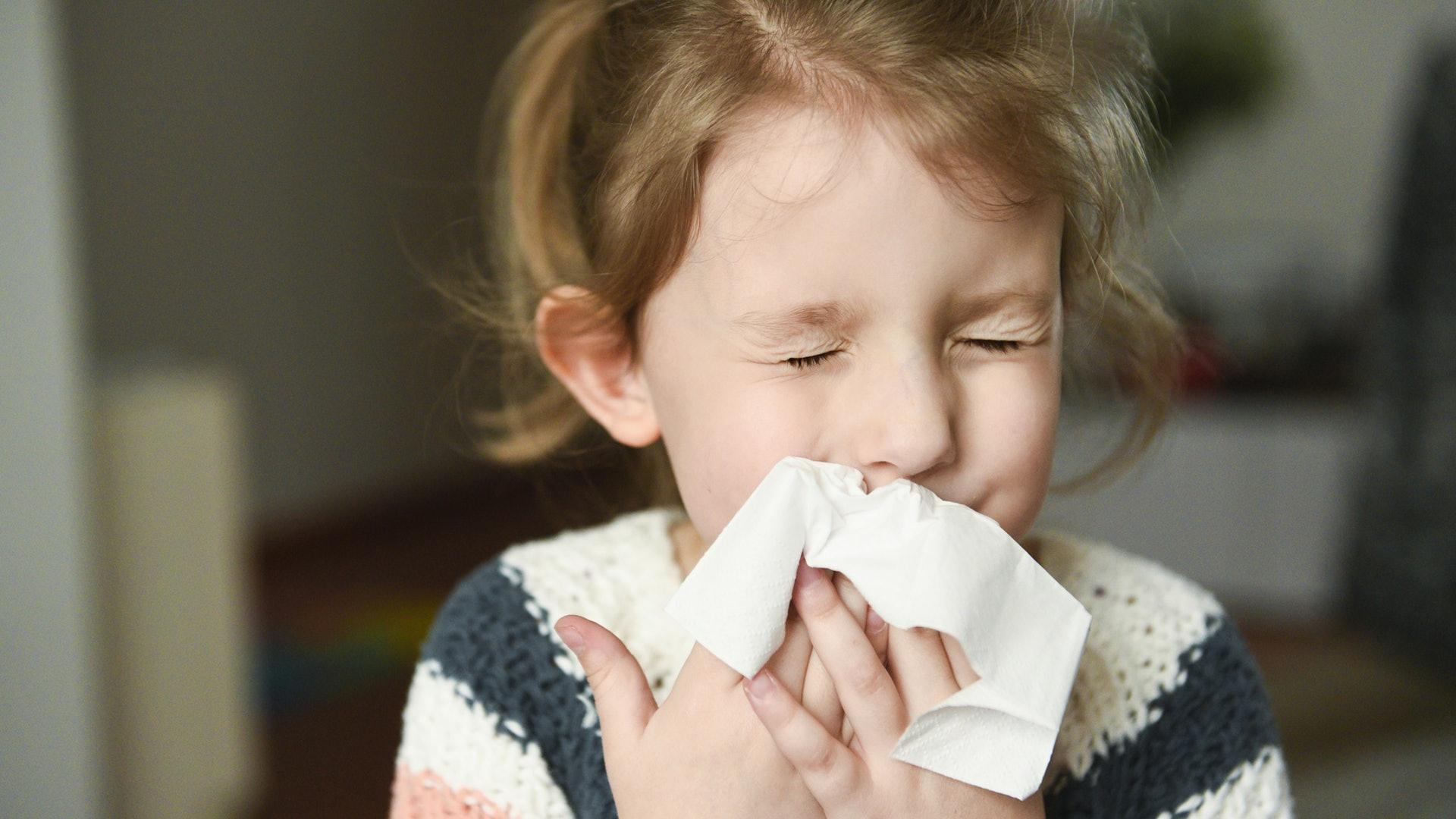 Child wiping nose because of pollen allergies