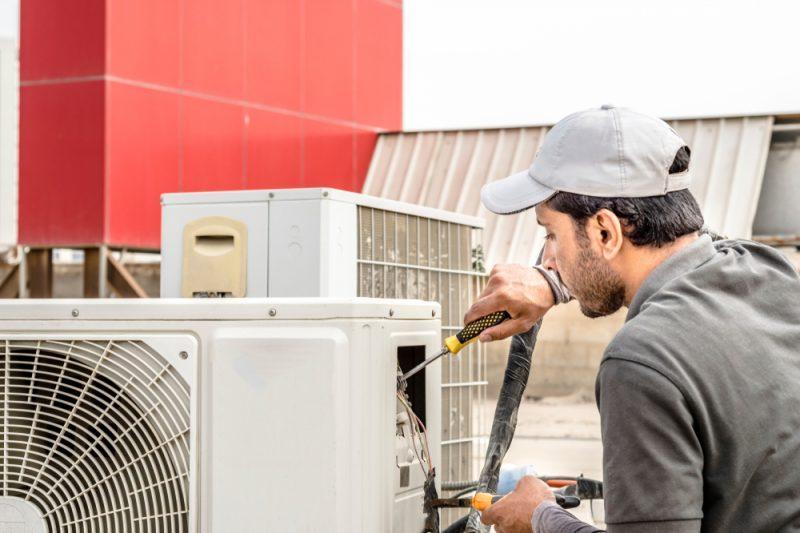 hvac service provider working on ac unit