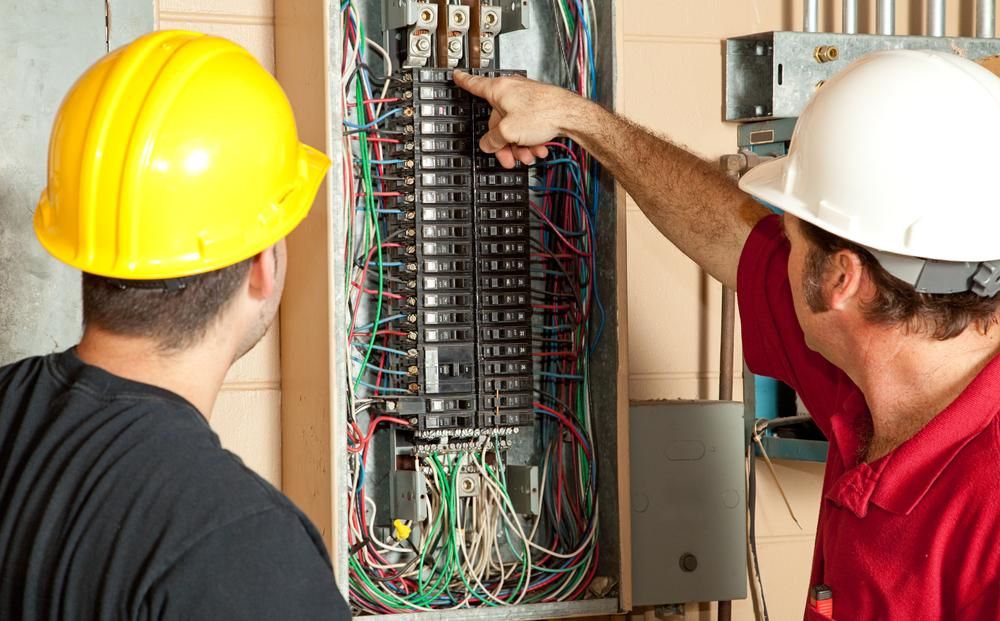 Electricians working on an electrical panel